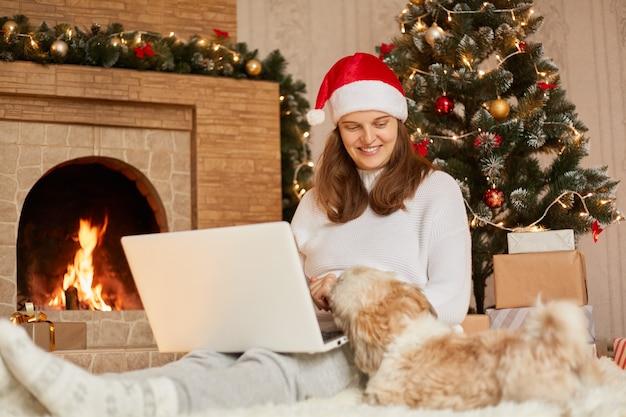 Charmant meisje met laptop en hond in de feestelijke woonkamer van kerstmis, dame die lachend naar haar huisdier kijkt, freelancer thuis werken tijdens vakantie, meisje met witte casual witte trui en rode hoed.