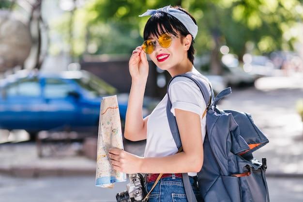 Charmant meisje met rode lippen houdt speels gele bril en lacht tijdens reis door de stad met rugzak
