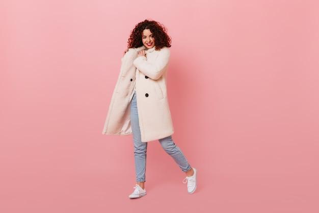 Charmant meisje met rode lippenstift die zich voordeed op roze ruimte. portret van krullende vrouw in witte wollen jas en lichte spijkerbroek.