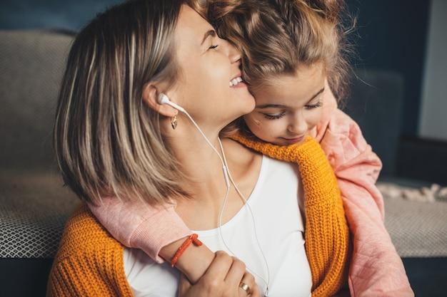 Charmant meisje omhelst haar moeder terwijl ze naar muziek op de vloer luistert