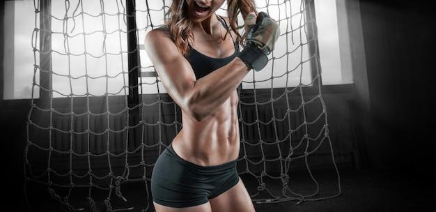 Charmant meisje traint in de sportschool met een rubberen band. het concept van bodybuilding, fitness, gezonde levensstijl. gemengde media