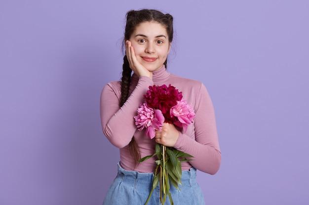 Charmant, mooi meisje met boeket pioenrozen in handen, poseren tegen lila muur, charmante dame met handpalm op wang, vrouw met prettige uitstraling en twee staartjes.