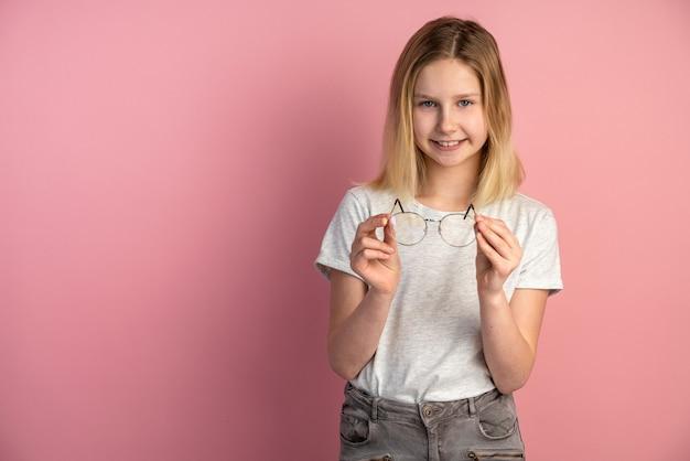 Charmant, mooi meisje met een bril in haar handen die zich voordeed op een lege muur