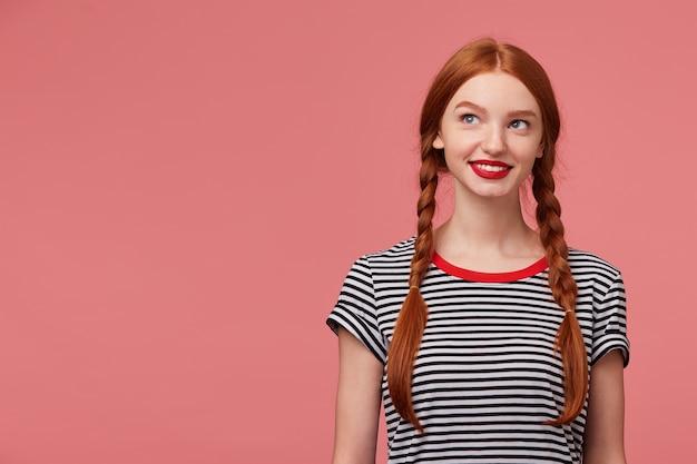 Charmant mooi mooi meisje met roodharige vlechten rode lippen, gekleed in een gestript t-shirt, glimlachend dromend bedachtzaam kijkt naar de linkerbovenhoek staat naast de lege kopie ruimte