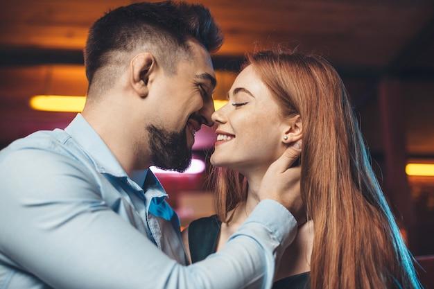 Charmant paar kussen en glimlachen naar elkaar daten op valentijnsdag