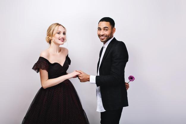Charmant paar verliefd valentijnsdag vieren. aantrekkelijke vrouw in luxe avondjurk, elegante knappe man in smoking met bloem achter rug. liefde, glimlachen, zweethartjes.