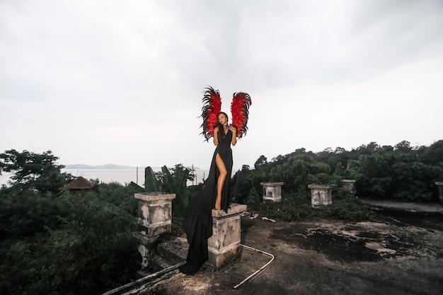 Charmant portret van donkere engel met rode sterke krachtige vleugels in zwarte kanten jurk en met koude ogen staande op het oude verpletterde gebouw, kunstfoto. buitenfoto met donkere kleuren