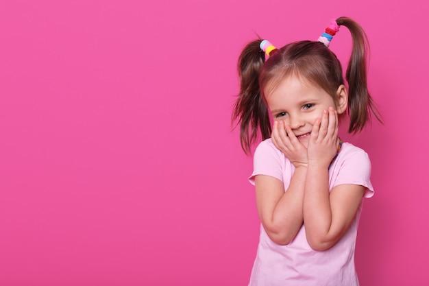 Charmant positief klein kind met twee paardenstaarten en veel kleurrijke scrunchies, gekleed in roze t-shirt, drukt aangename emoties uit, houdt beide handen op de wangen.