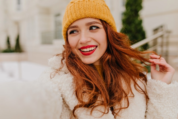 Charmant roodharig meisje dat van de winter geniet. buiten foto van zorgeloze kaukasische dame selfie maken in koude dag.