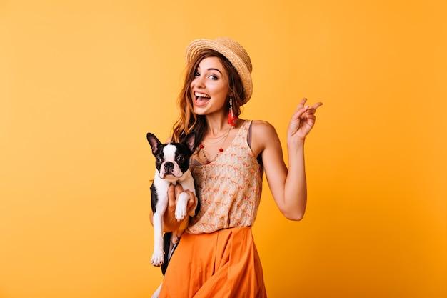 Charmant roodharig meisje in vintage hoed met franse bulldog. binnenportret van het verbaasde witte vrouw stellen op geel met puppy.