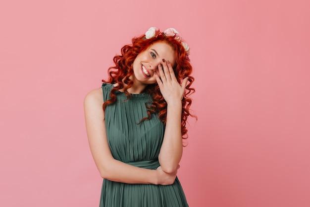 Charmant roodharig meisje met bloemen op haar hoofd lacht lief en bedekt haar gezicht met haar hand. portret van dame in groene outfit op roze ruimte.