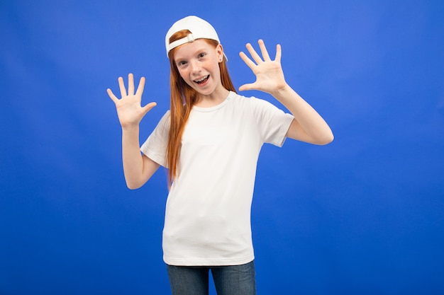 Charmant roodharig tienermeisje in een wit t-shirt toont een lege printruimte op een blauwe studio