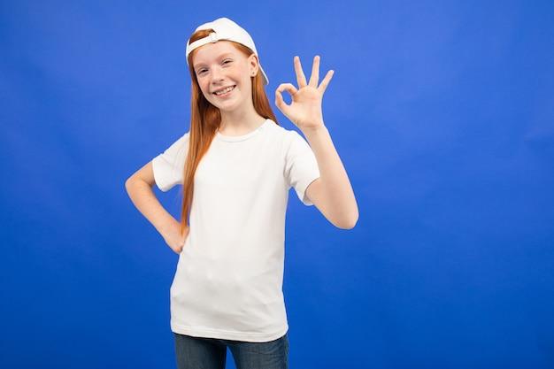 Charmant roodharig tienermeisje in een wit t-shirt toont een lege printruimte op een blauwe studioachtergrond