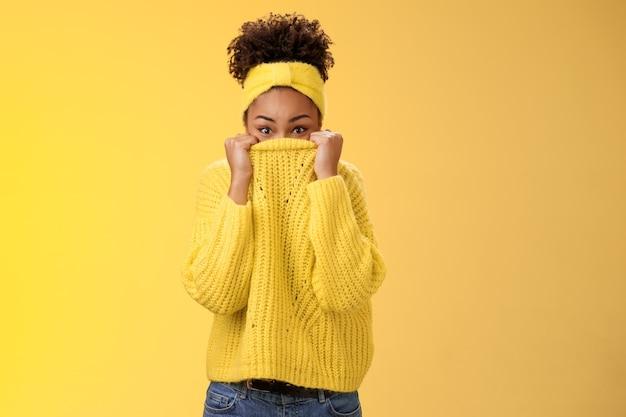 Charmant, schattig, dom jong afro-amerikaans modern meisje dat een trui op het gezicht trekt die zich verstopt in een glurende camera die speels plezier heeft met lachende verstoppertje dwaas rond het nabootsen van een staande gele achtergrond.