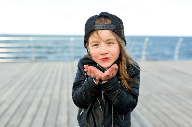 Charmant schattig klein meisje gekleed in een stijlvolle jas en pet stuurt een kus