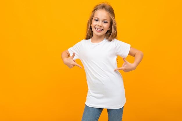 Charmant schoolmeisje op een oranje in een wit t-shirt gebaart naar zichzelf