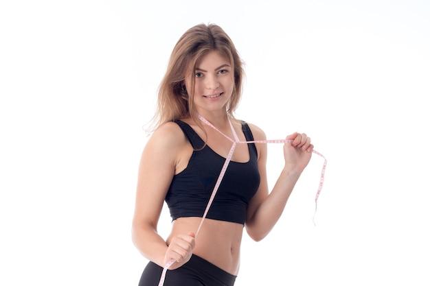 Charmant sportmeisje dat lacht en een meetlint om haar nek gespannen houdt