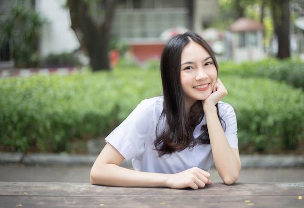 Charmant tiener aziatisch meisje die op universitaire eenvormige student glimlachen