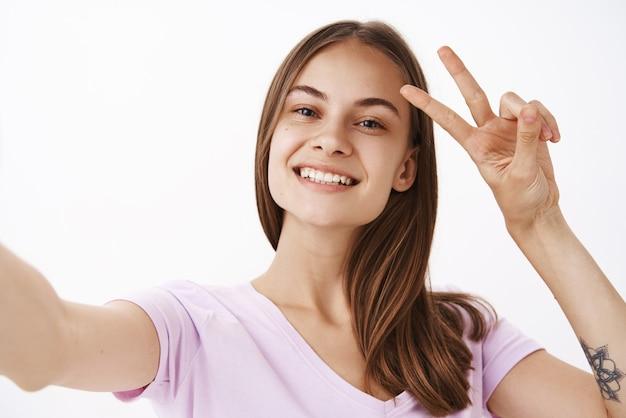 Charmant vriendelijk ogend vrolijk meisje met bruin haar glimlachend in grote lijnen met vrede of overwinningsteken dichtbij gezicht terwijl ze selfie met smartphone over grijze muur neemt