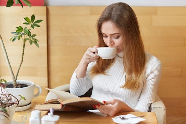 Charmant, vrolijk meisje neemt een slokje thee, leest een actievol boek en richt alle aandacht op het plot. jong model zit in de buurt van groene planten en warme koffie op tafel.