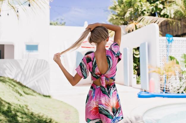 Charmant vrouwelijk model in elegante zomerkleding die afstand in zomerdag bekijkt.