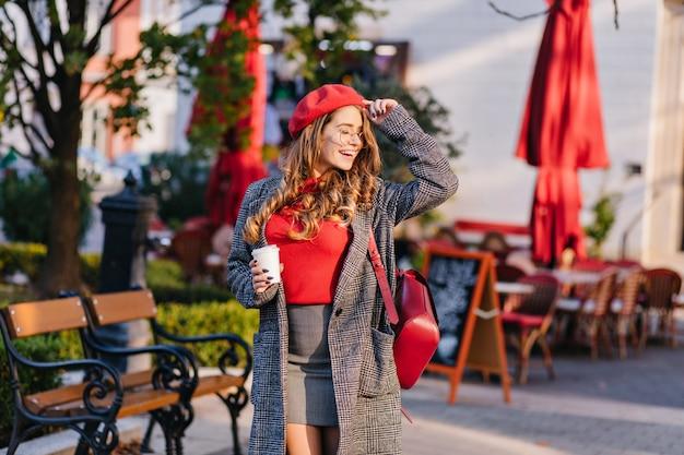 Charmant vrouwelijk model in minirok poseren met gesloten ogen in zonnige dag op straat in de buurt van café