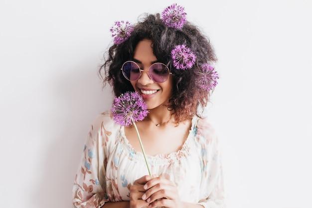 Charmant vrouwelijk model met donkere huid die allium vasthoudt en geluk uitdrukt. binnenfoto van knappe stijlvolle vrouw met bloem.