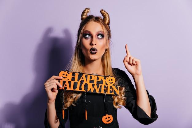 Charmant wit meisje met griezelige make-up poseren met halloween-decor. schitterende europese dame in vampieruitrusting die zich op paarse muur bevindt.