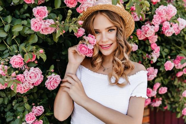 Charmant wit vrouwelijk model dat zich voor roze bloemen bevindt. outdoor portret van vrolijk meisje in trendy hoed tijd doorbrengen in de tuin.