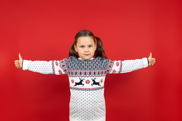 Charmant zesjarig meisje in witte kersttrui met rendieren die duimen opgeven en met armen sp...