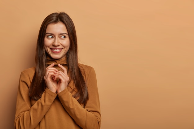 Charmante, aangenaam uitziende vrouw houdt de handen bij elkaar, kijkt opzij, heeft een nieuwsgierige intentie of een geweldig plan, gekleed in vrijetijdskleding, geïsoleerd op een bruine muur, kopieer ruimte voor uw reclametekst