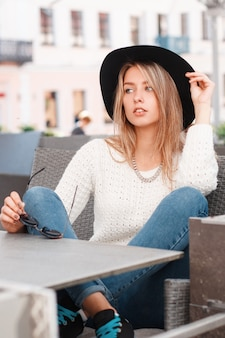 Charmante aantrekkelijke jonge vrouw in een vintage witte trui in stijlvolle spijkerbroek in sneakers in een elegante zwarte hoed zit op de bank aan een grijze tafel in een straatcafé op een warme lentedag. leuk meisje.