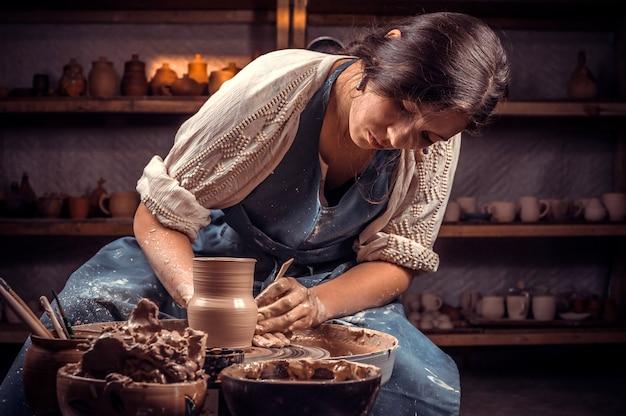 Charmante ambachtsman meester bezig met pottenbakkerswiel met ruwe klei met handen