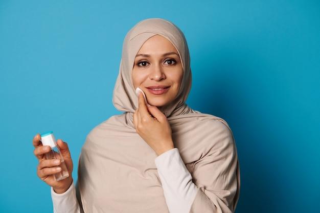 Charmante arabische vrouw in hijab houdt een wattenschijfje en reinigt haar gezicht, glimlacht terwijl ze naar de camera kijkt.
