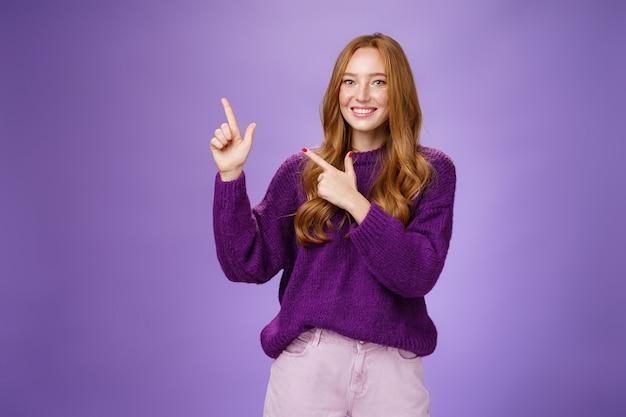 Charmante assertieve vrouwelijke winkelbediende die naar de linkerbovenhoek wijst om een cool product te promoten dat breed glimlacht, zich vrolijk en opgewonden voelt en een vriendelijke houding uitdrukt als poseren in een paarse trui.
