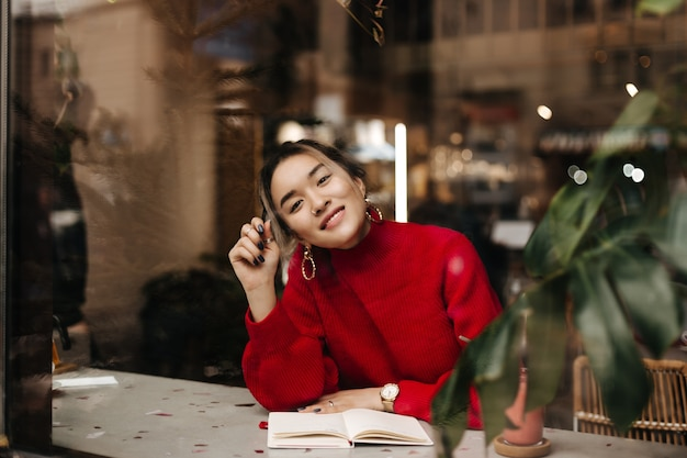 Charmante aziatische vrouw in rode gebreide outfit en enorme oorbellen glimlacht zittend in café met laptop op tafel