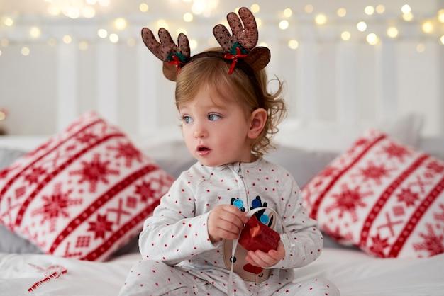 Charmante baby die het kerstcadeautje in bed opent