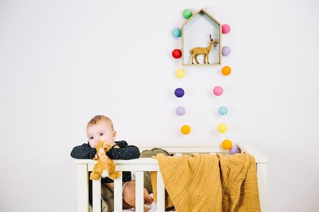 Charmante baby in wieg kauwende stuk speelgoed