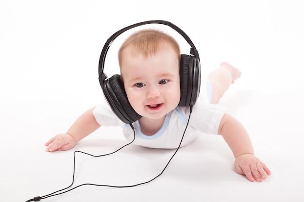 Charmante baby op een wit met koptelefoon luisteren naar