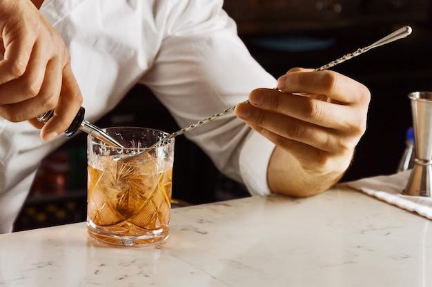 Charmante barman bereidt op elegante wijze een mixdrankje door alle ingrediënten in een barlepel te gieten. gemengde media