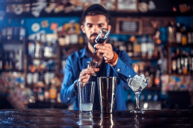 Charmante barman maakt een show en maakt een cocktail aan de bar