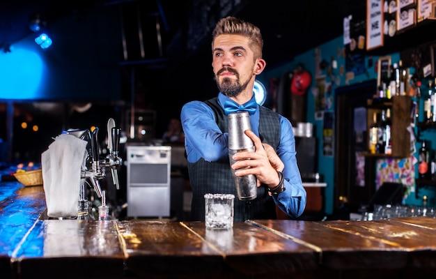 Charmante bartending demonstreert zijn vaardigheden over de toonbank