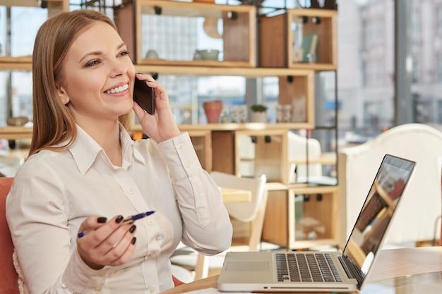 Charmante bedrijfsvrouw die op de telefoon bij koffiewinkel spreekt