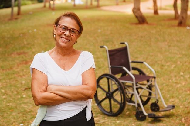 Charmante bejaarde vrouw lachend in het park staan met de rolstoel in de
