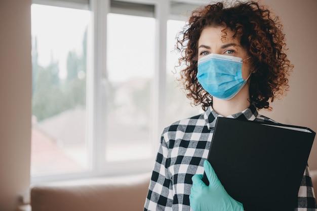 Charmante blanke arts met krullend haar die enkele documenten vasthoudt en n95-gezichtsmasker met handschoenen draagt