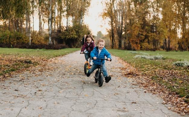Charmante blanke broers en zussen vermaken zich tijdens een herfstwandeling in het park terwijl ze fietsen