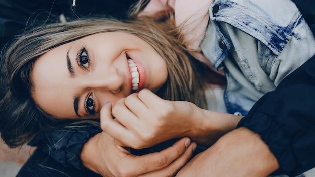 Charmante blanke dame met een vrolijke brede glimlach ligt op haar vriendje dat door hem wordt omarmd