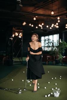 Charmante blanke dame poseert voor de camera en speelt golf, foto geïsoleerd op donkere achtergrond wazig