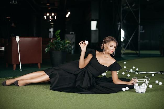 Charmante blanke dame poseert voor de camera en speelt golf, foto geïsoleerd op donkere wazige achtergrond Gratis Foto