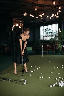 Charmante blanke dame poseert voor de camera en speelt golf, foto geïsoleerd op donkere wazige achtergrond